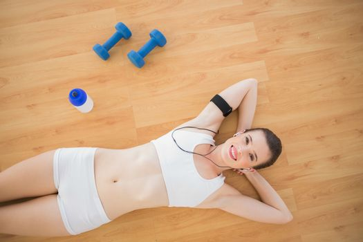 Beautiful fit brown haired model in sportswear listening to music lying on wooden floor