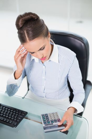 Concentrating businesswoman using calculator