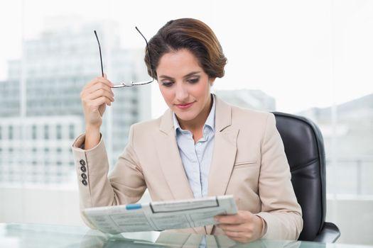 Content businesswoman reading newspaper