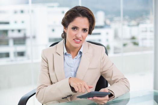 Annoyed businesswoman using calculator