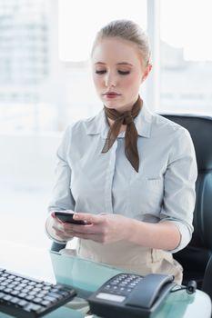 Blonde stern businesswoman using smartphone