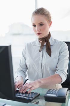 Blonde stern businesswoman working on computer