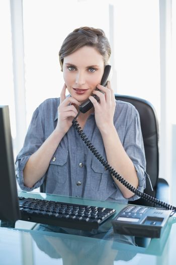 Cute young businesswoman phoning with telephone sitting at desk