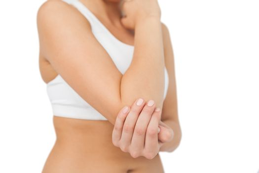 Young sporty woman touching her sore elbow