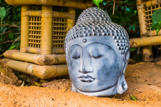 buddha head sculpture in closeup, traditional spiritual decoration