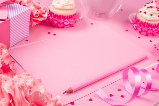 Valentines day pink background with blank love letter with copy space gift box rose flowers cupcakes pencil and drink