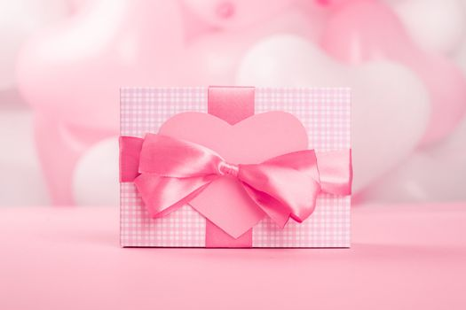 Valentine Day gift in a box wrapped in striped paper and tied with silk ribbon bow and heart shaped greeting card on pink balloons background with copy space for text