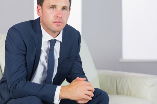 Stern handsome businessman relaxing on couch