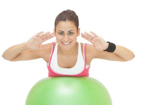 Happy sporty brunette doing exercise on exercise ball