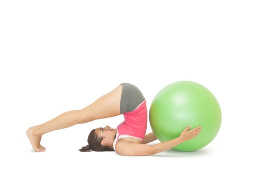 Attractive sporty brunette doing pilates exercise