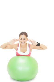 Lucky sporty brunette doing exercise on exercise ball
