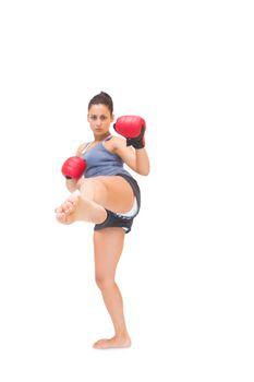 Stern sporty brunette kick boxing