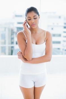 Unsmiling toned brunette phoning