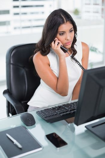 Unsmiling cute businesswoman phoning
