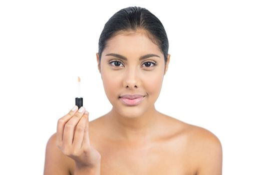 Pleased nude brunette holding lip gloss