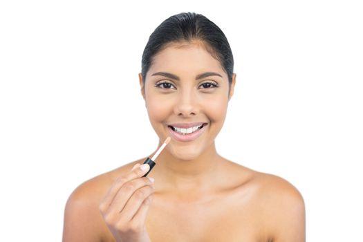 Smiling nude brunette holding lip gloss