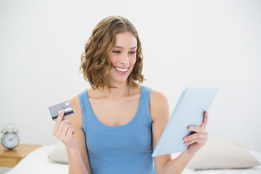 Gorgeous woman holding her tablet and debit card sitting on her bed