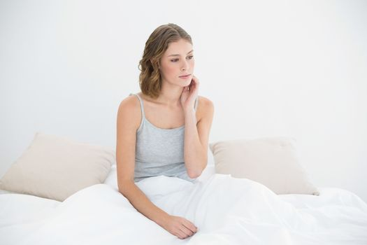 Thoughtful slender woman sitting under the cover on her bed