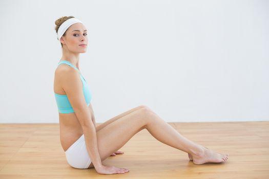 Pretty slender woman sitting on floor in sportswear