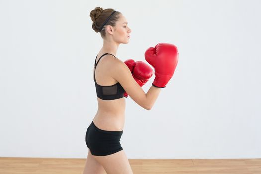 Pretty sporty woman wearing boxing gloves posing in sports hall
