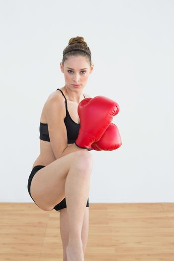 Lovely fit woman wearing red boxing gloves posing in sportswear in sports hall