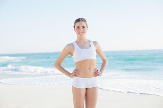 Smiling slender woman standing hands on hips