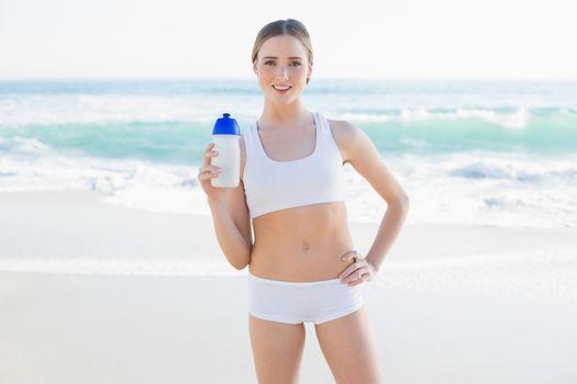 Cheerful slender woman holding sports bottle