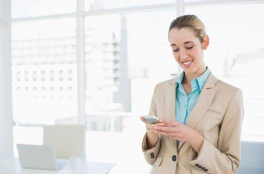 Content classy businesswoman texting with her smartphone