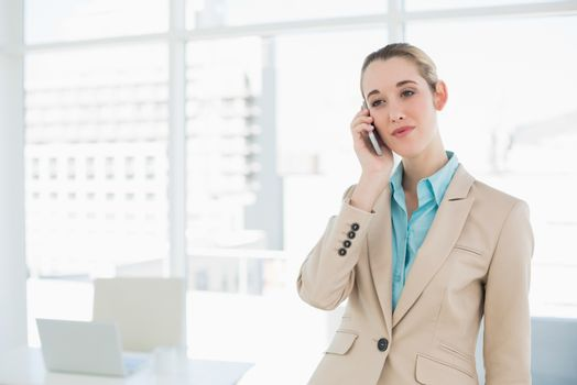 Concentrated classy businesswoman phoning with her smartphone