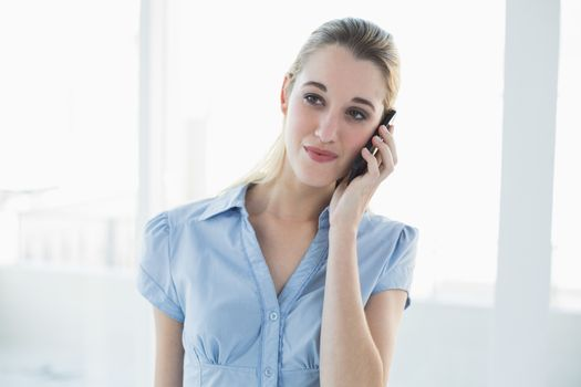 Smiling classy businesswoman phoning with her smartphone