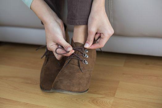 Slender woman tying her shoelaces