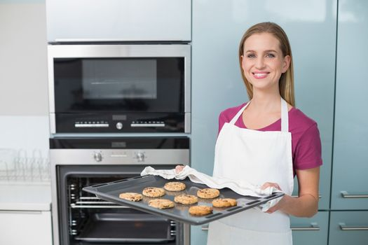Casual happy woman holding baking tray with cookies