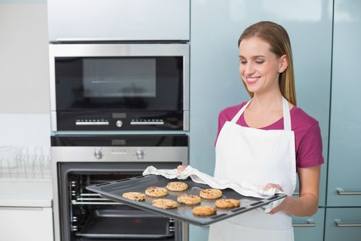 Casual smiling woman holding baking tray with cookies