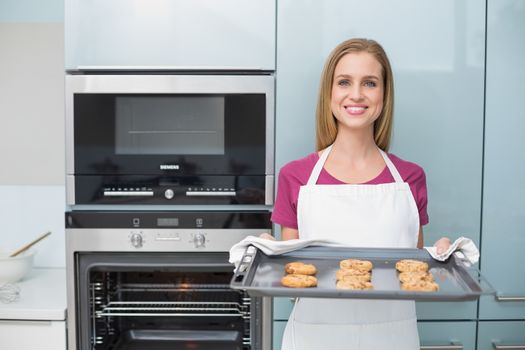 Casual attractive woman holding baking tray with cookies