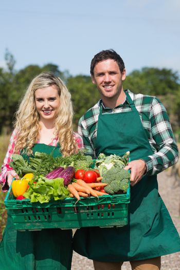 Proud couple showing vegetables in a basket