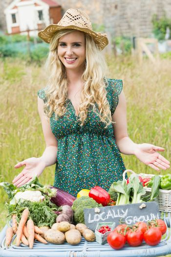Blonde woman presenting her vegetables to sell