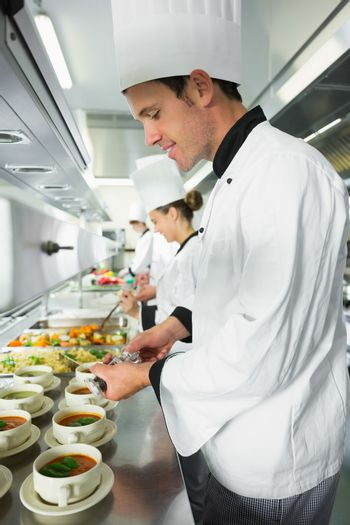 Smiling handsome chef seasoning his soup