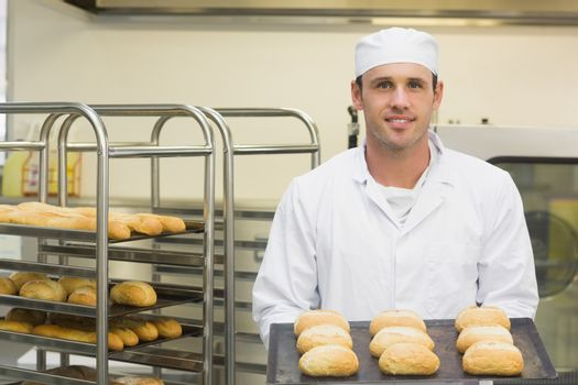 Happy young baker holding some rolls on a baking tray