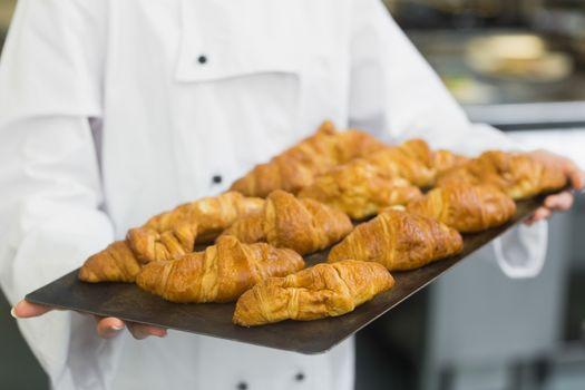 Baker presenting some croissants
