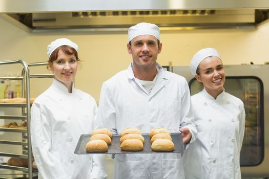 Young male baker holding a baking tray with rolls on it