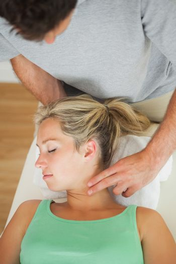 Physiotherapist putting pressure to patients turned neck