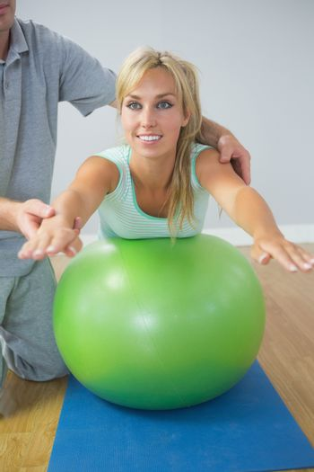 Physiotherapist holding patient doing exercise on exercise ball