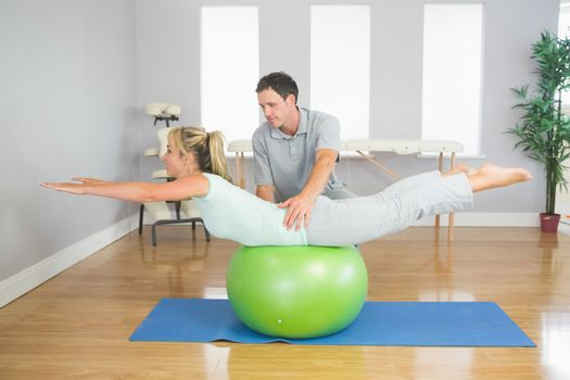 Physiotherapist helping patient doing exercise with exercise ball