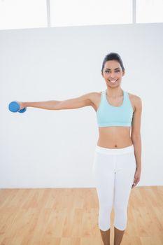 Cheerful slender woman lifting blue dumbbell