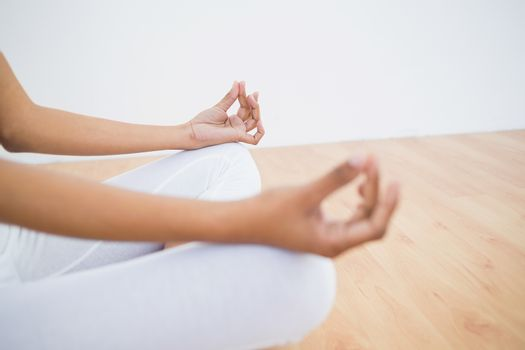 Mid section of slender young woman meditating