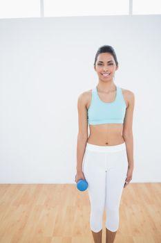 Cute slender woman holding blue dumbbell