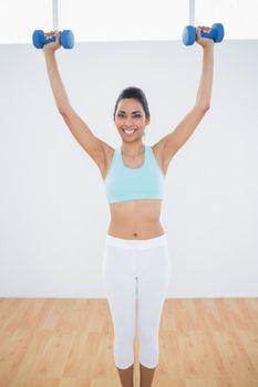 Content slender woman lifting blue dumbbells