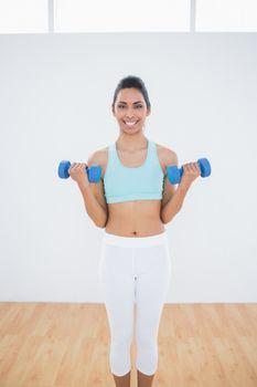 Beautiful slender woman lifting blue dumbbells