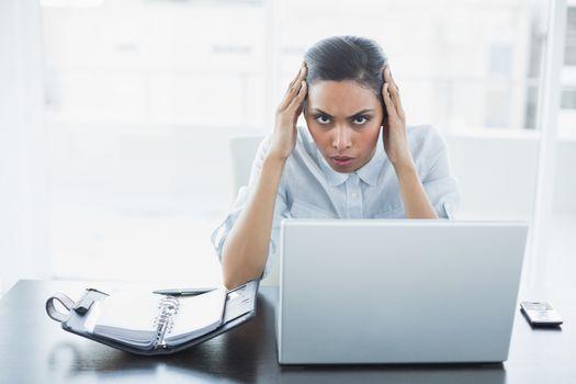 Lovely stern businesswoman suffering from headache