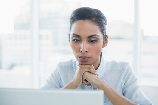 Concentrating businesswoman sitting at her desk